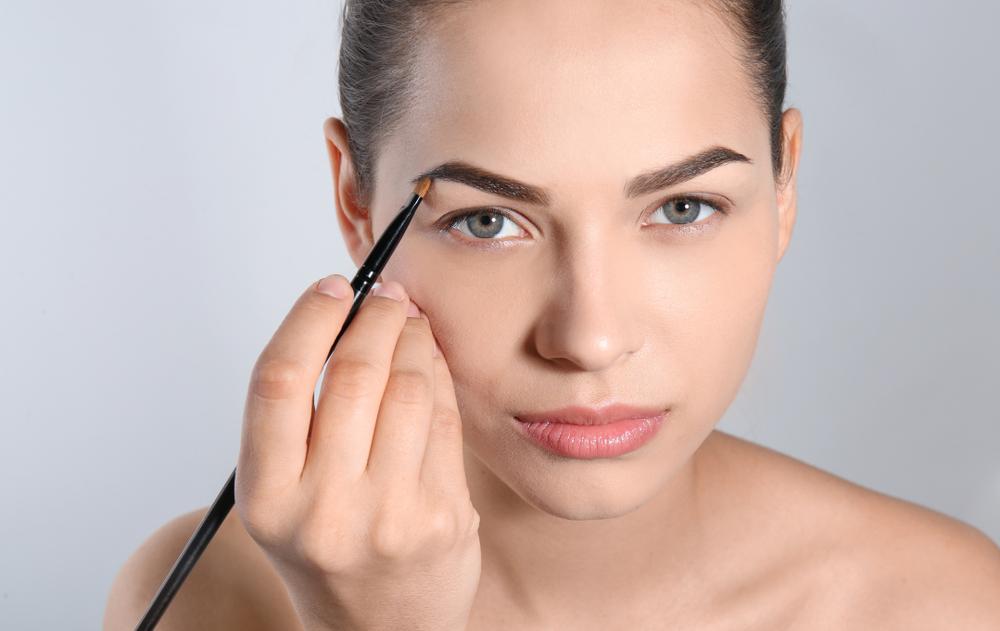 ブラシで眉毛を描いている女性
