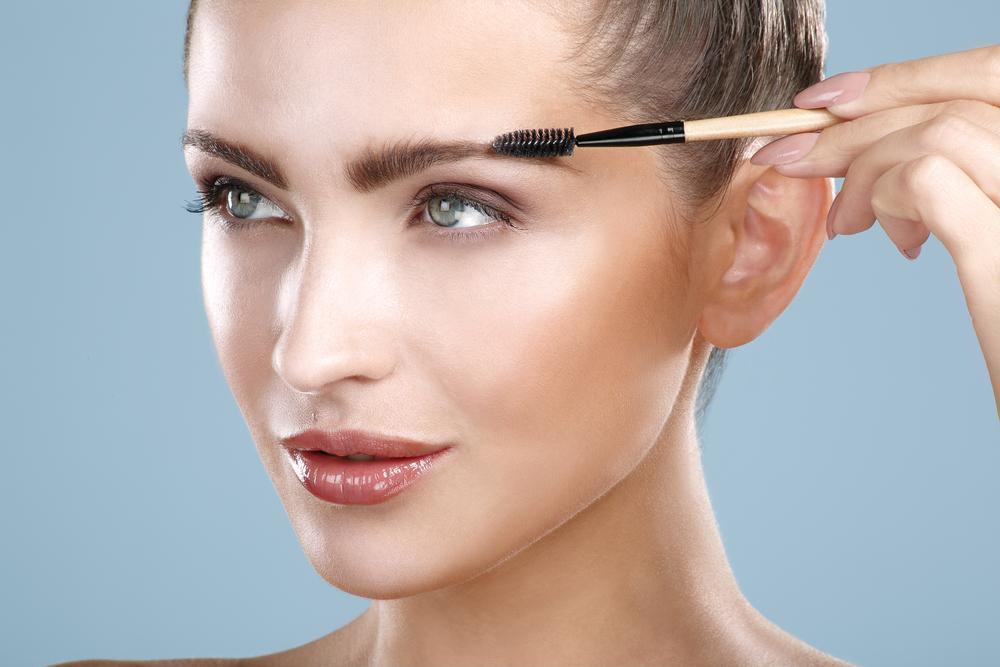 眉毛をブラシでとかしている女性
