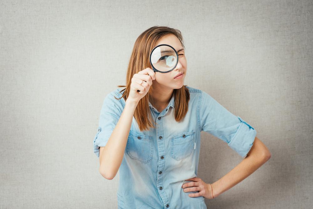 虫眼鏡で覗く女性
