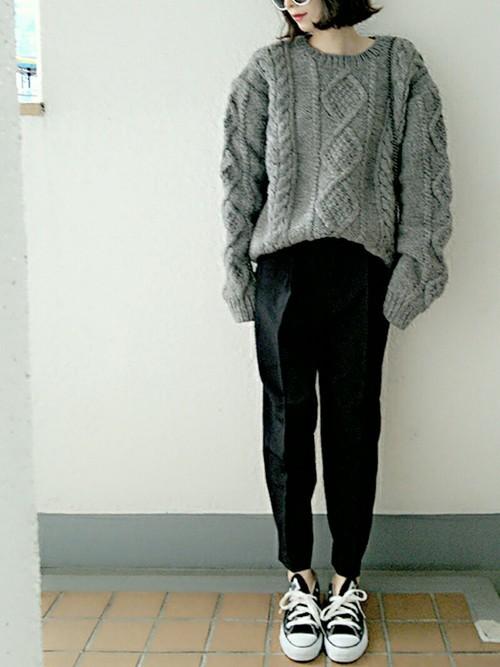 グレーのケーブル編みセーターと黒のクロップドパンツのコーデ