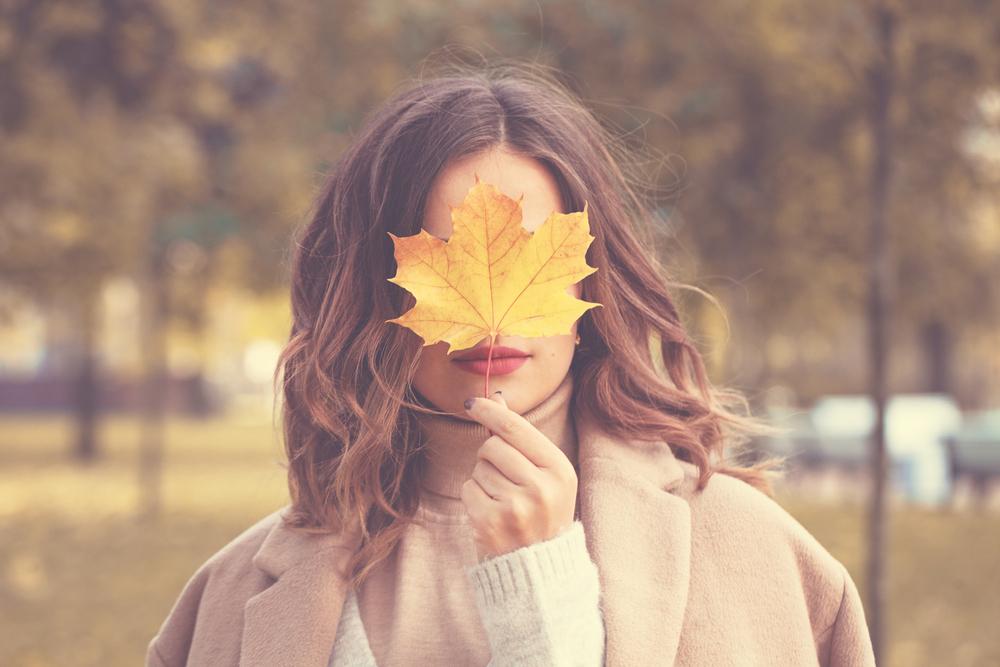 落ち葉で顔を隠す女性