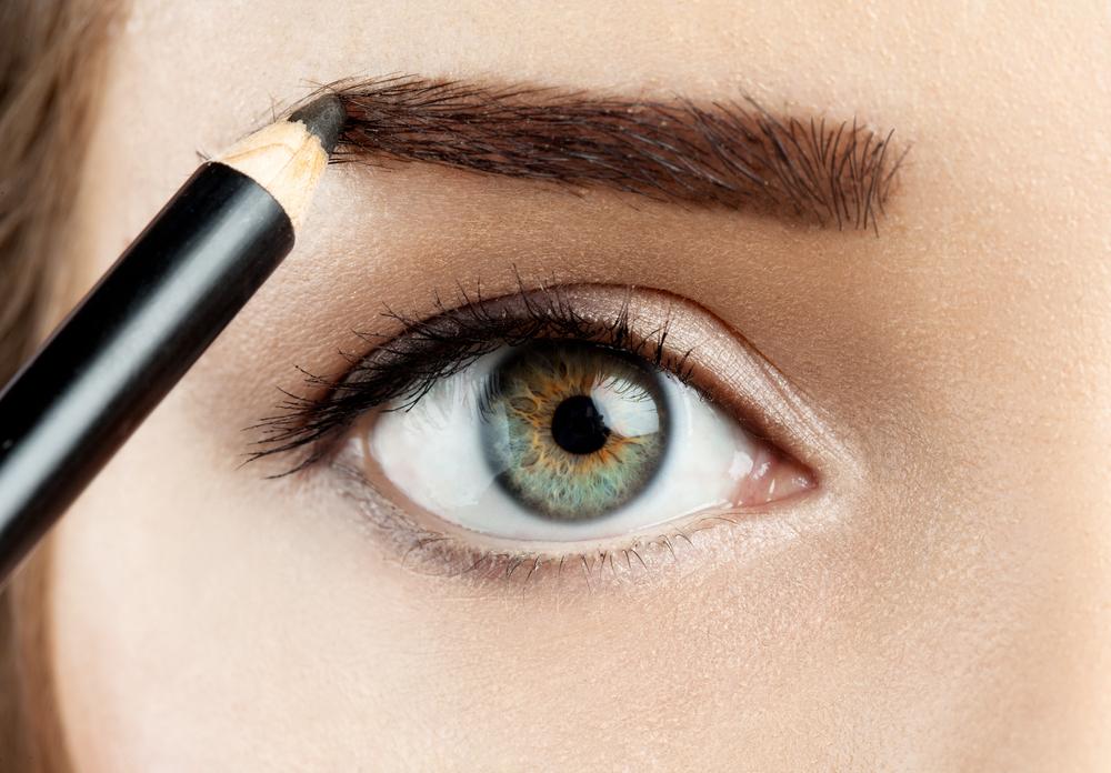 ペンシルで眉毛を描く女性