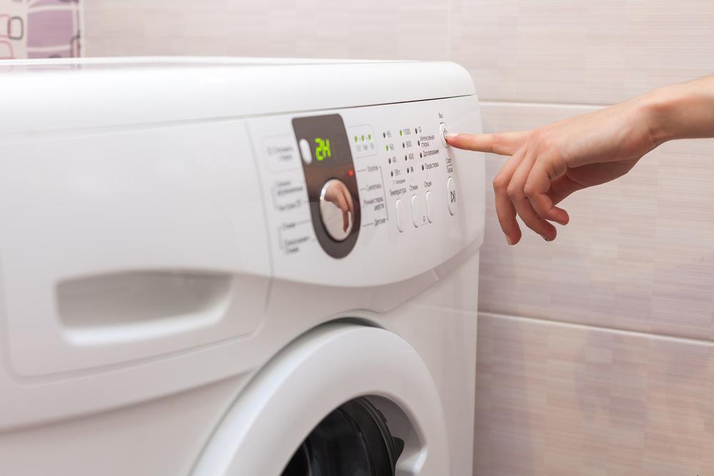 洗濯機で選択する女性の手元